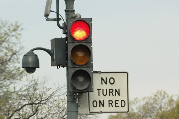 Semáforo rojo con cartel redundante