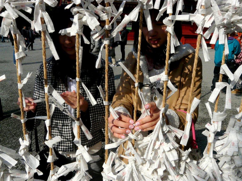 Chicas japonesas anudando papelitos en templo japonés - versión original