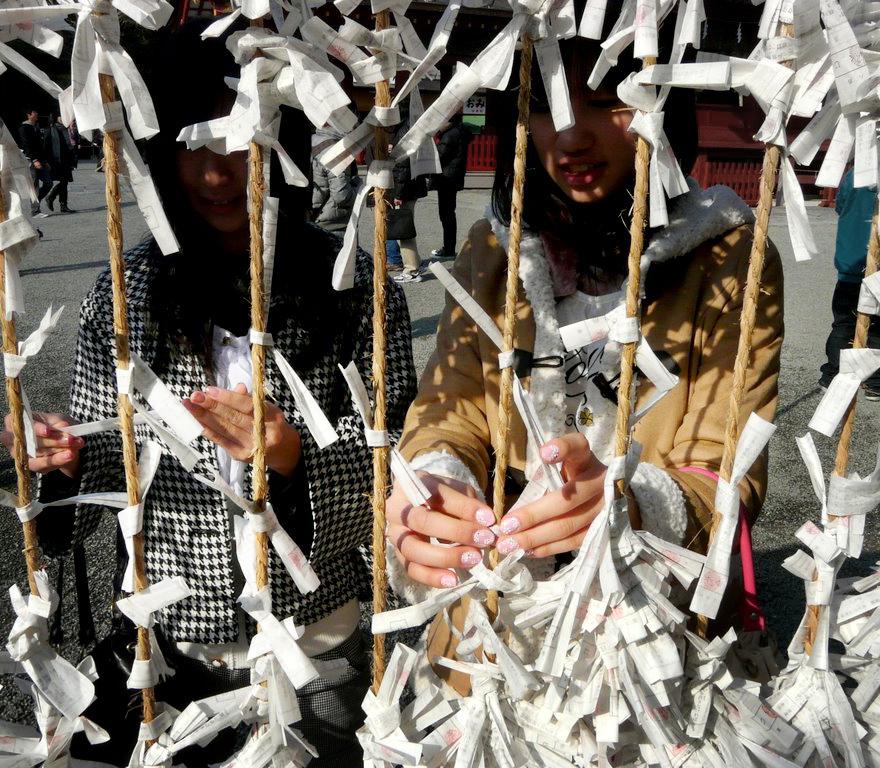 Chicas japonesas anudando papelitos en templo japonés