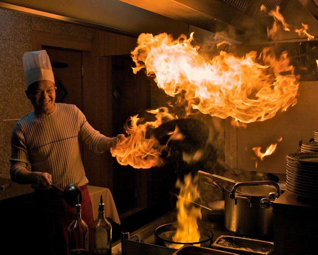 Cocinero oriental con wok en llamas