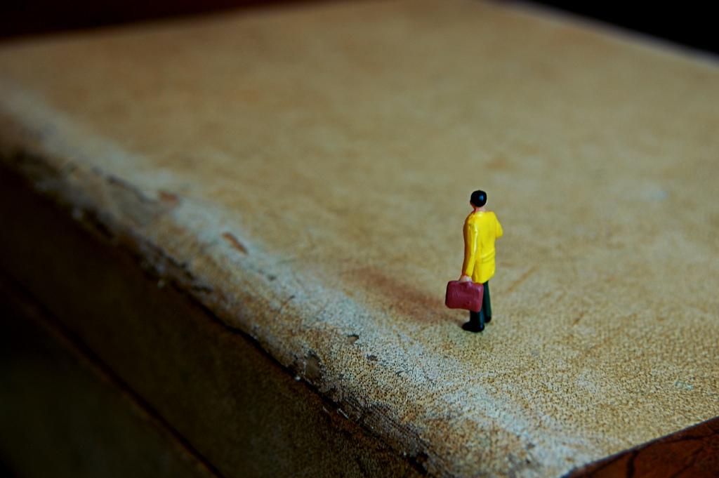 Figura en miniatura de hombre con maleta
