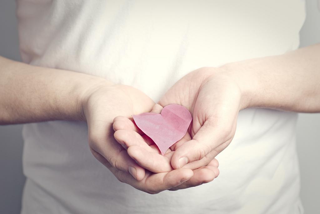 Corazón de papel sujeto por dos manos