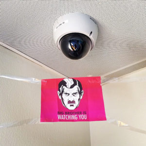 "Cámara de vigilancia y cartel con texto ""Big Brother is watching you"""